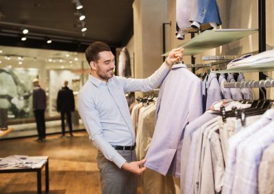 happy young man choosing clothes in clothing store
